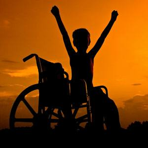 Boy in wheelchair with raised arms symbolising freedom, independence and overcoming